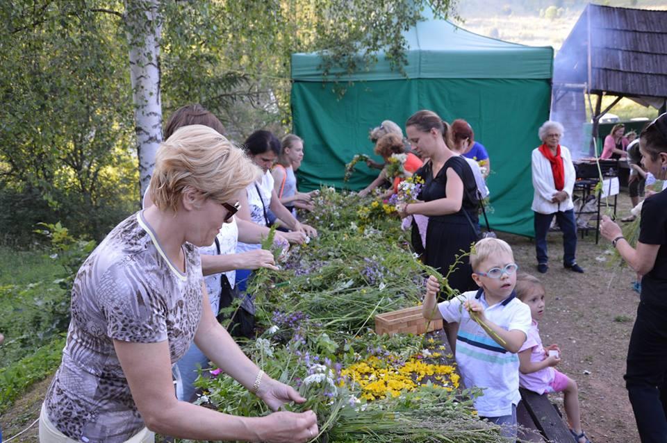 Stół z kwiatami i grupa osób plotących wianki